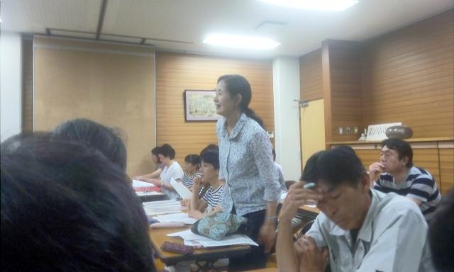 記念誌の校正作業を終了した旨を報告する編集委員長代理の高橋さん